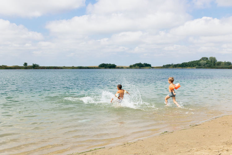 Boys with water wings running at beach against sky