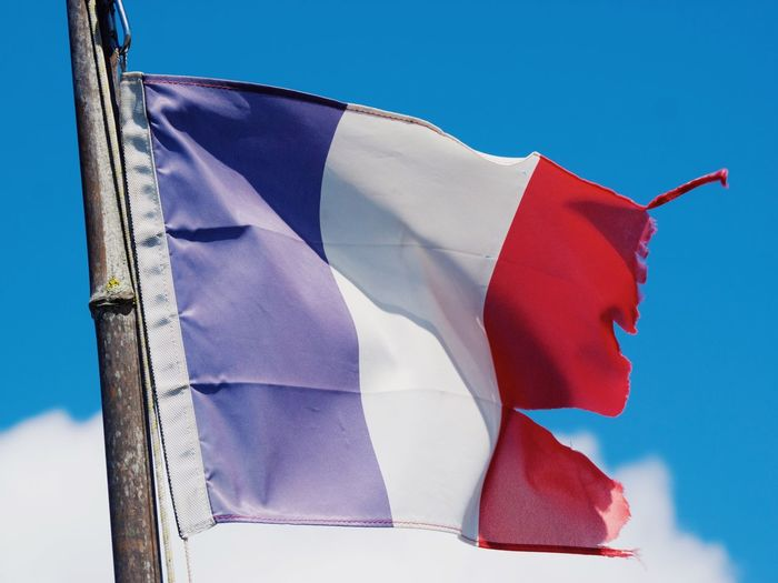 Low angle view of torn french flag against blue sky