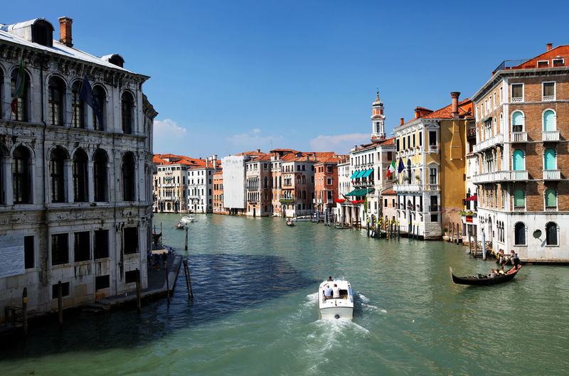 Gondolas moving on grand canal amidst buildings against clear blue sky