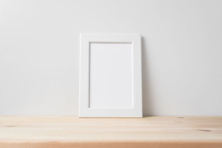 Close-up of white wooden table against wall
