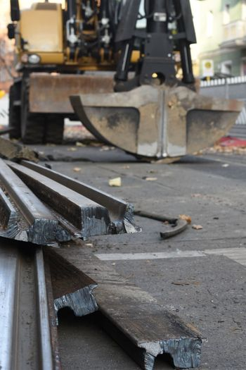 Close-up of pile of metal tracks against mechanical digger