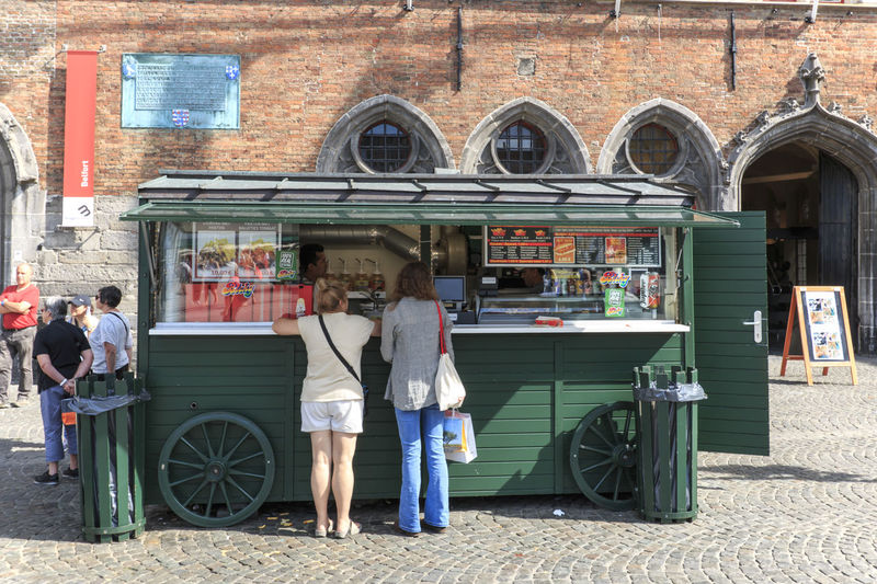 Bruges, Belgium - July 7, 2017: Tourists in front of a stand selling french fries in the market square in the center of Bruges, a beautiful medieval town in Belgium Beer Belgium Brugge Chocolate Dijver Canal Duvel Flanders Panoramic View Provinciaal Hof West Flanders Aerial View Belfry Tower Bikes Bruges Europe Flower French Fries Holland Market Square Medieval Town Mussels