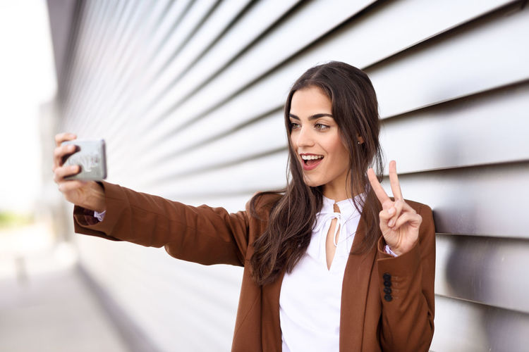 Young businesswoman taking selfie while gesturing peace sign by blinds