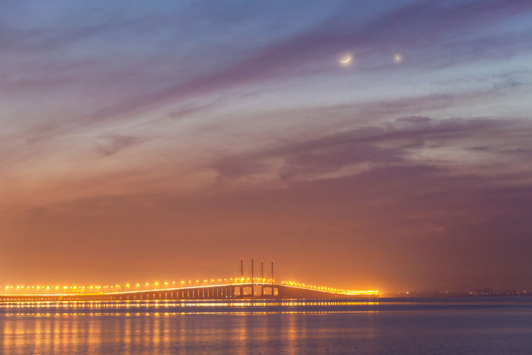 Illuminated Bridge Over Sea Against Cloudy Sky At Night