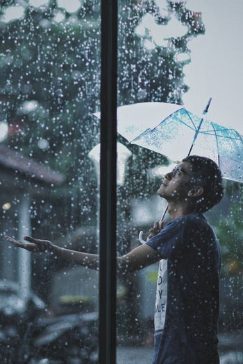 Man holding umbrella in rain seen through window