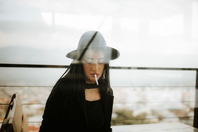 Woman Wearing Hat Seen Through Window