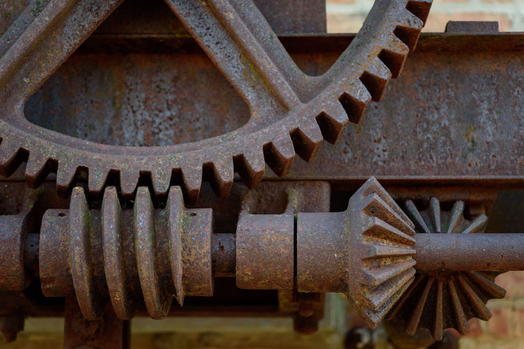 Closeup of old rusted steel gears shafts and pinions outside old industrial factory Antique Industrial Weathered Background Beam Close-up Day Differential Gear Industry Large Machine Part Machinery Manufacturing Equipment Metal No People Pattern Pinion Pitted Rusted Rusty Shaft Sprocket Steel Teeth