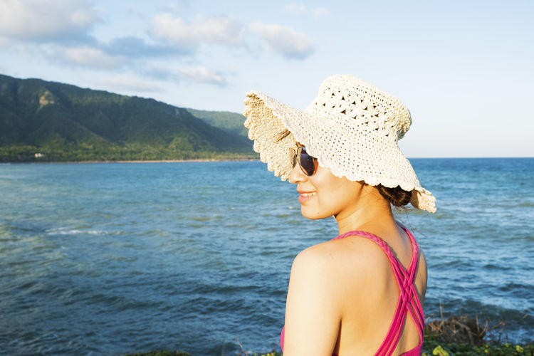 Woman Wearing Hat Standing By Sea
