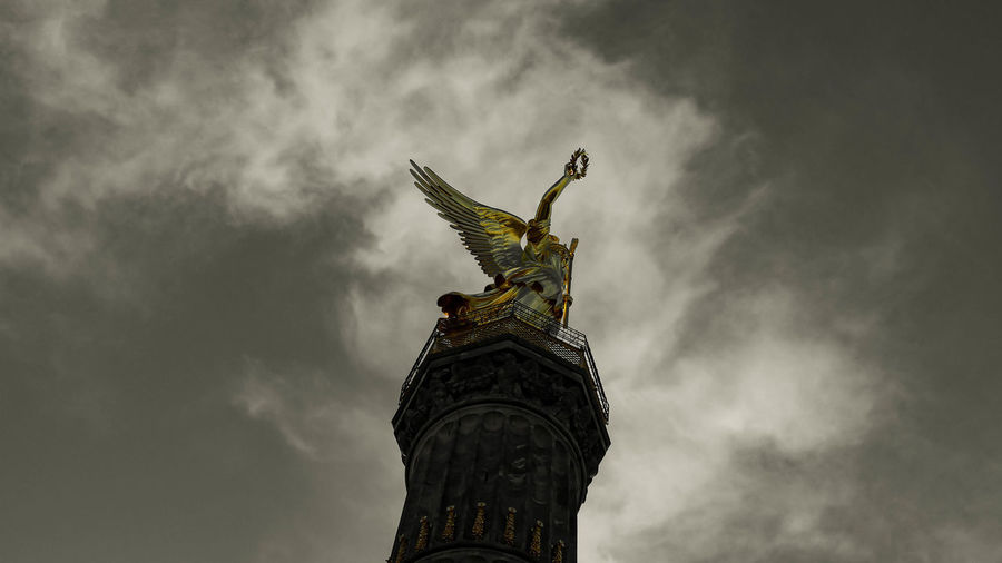 Low angle view of angel statue against cloudy sky