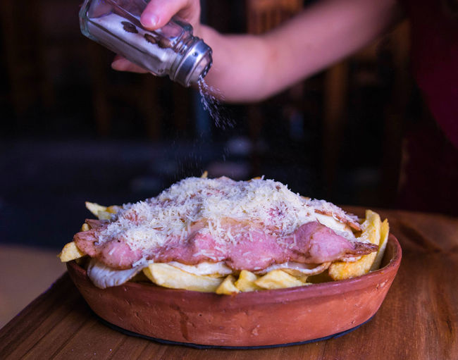 Plate of fried potatoes with bacon, cheese and eggs. Food Food And Drink Human Hand One Person Hand Preparation  Preparing Food Table Real People Fries Fried Potatoes Delicious Tasty Bacon Cheese Eggs Horizontal Wood Table Salt Salt Shaker