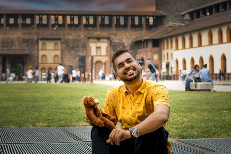 Portrait of cheerful young man holding toy animal while sitting against building