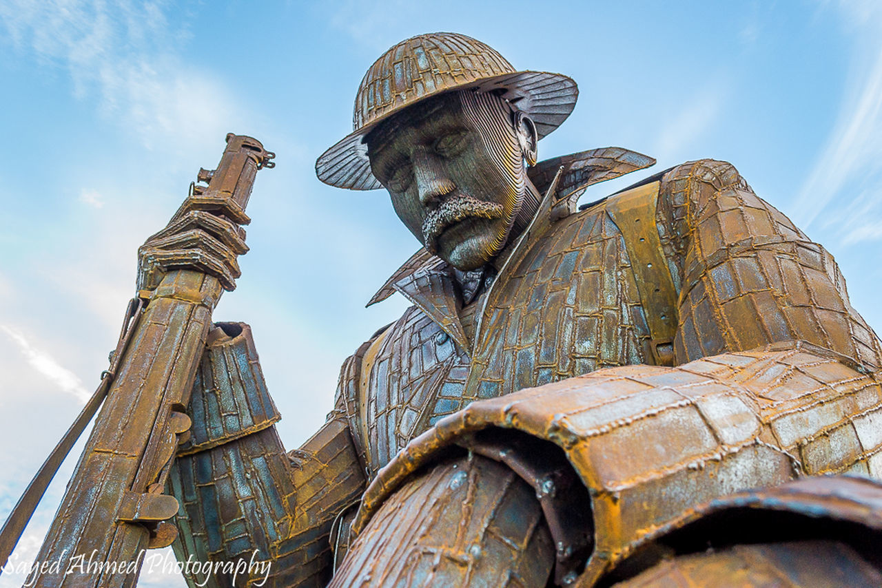 statue, low angle view, day, outdoors, sky, sculpture, no people, close-up, drilling rig