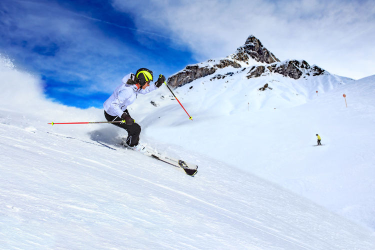 Female ski driver on the piste in Alps by Lech, Austria. A Cold, Activity, Adventure, Alpine, Alps, Area, Day, Extreme, Fun, Hobbies, Joy, Landscape, Leisure, Mountains, Moving, Nature, Outdoors, Person, Resort, Rocky, Ski, Ski Driver, Skidriver, Skiing, Sky, Snow, Snowboard, Snowboarder, Speed, Sports, Sportsm Sport Mountain Winter Cold Temperature Snow Winter Sport Leisure Activity Adventure Mountain Range Vacations Skiing One Person Holiday Trip Sports Equipment Lifestyles Sky White Color Day Ski-wear Skill  Snowcapped Mountain Ski Holiday Outdoors