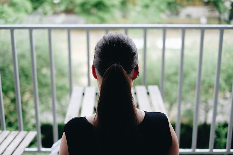 Rear view of woman with ponytail sitting at balcony