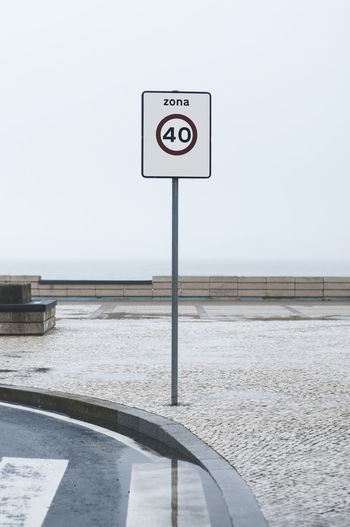 road sign at the atlantic 40 Asphalt Atlantic Ocean Cloudy Crosswalk Gray Sky Sidewalk Sign Traffic Transportation Travel Zona Cobblestone Communication Day Furadouro No People Outdoors Road Sign Sea Sky Speedlimit Street Symbol Zebra Crossing Modern Workplace Culture
