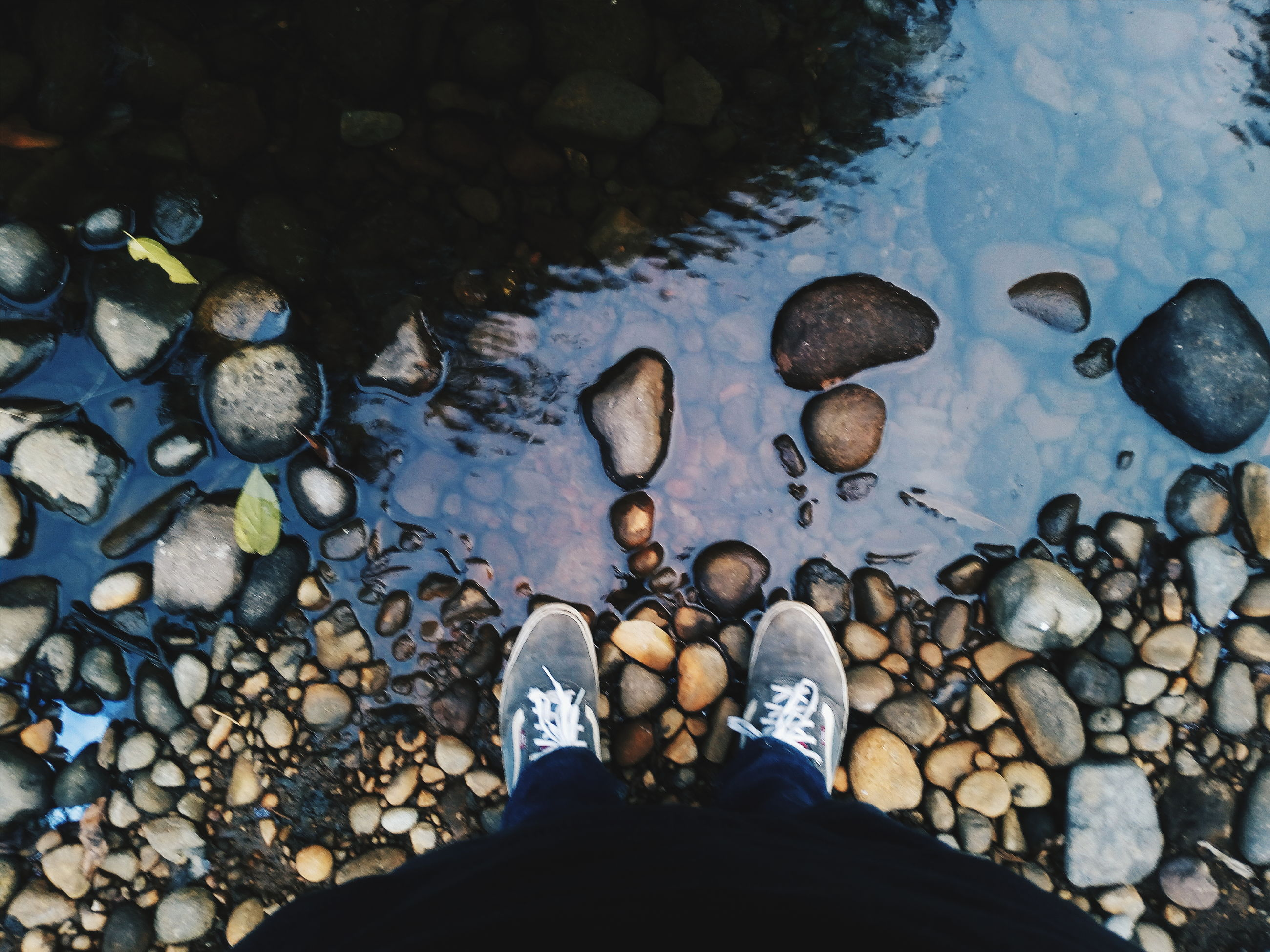 water, low section, person, standing, personal perspective, stone - object, shoe, rock - object, lifestyles, pebble, high angle view, leisure activity, men, nature, reflection, lake, outdoors