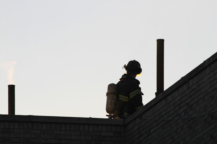 Low angle view of firefighter against clear sky