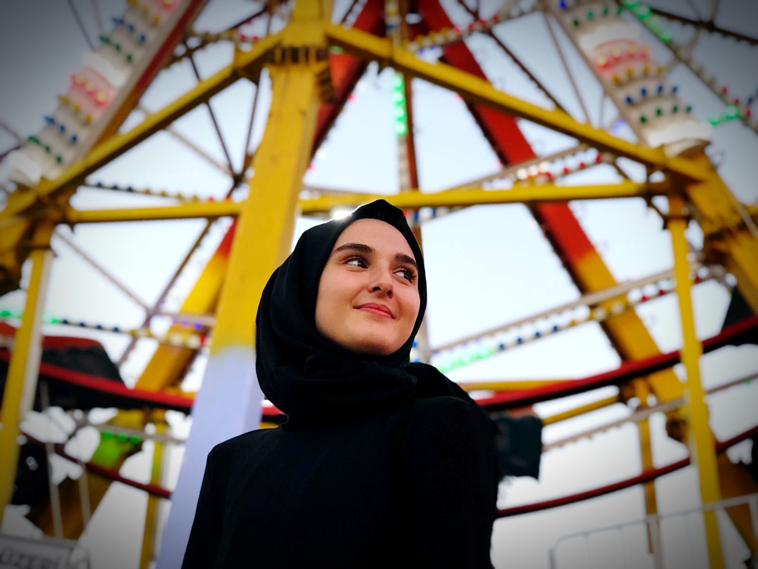 real people, one person, lifestyles, portrait, leisure activity, young adult, young women, smiling, waist up, amusement park ride, amusement park, low angle view, casual clothing, happiness, focus on foreground, front view, standing, arts culture and entertainment