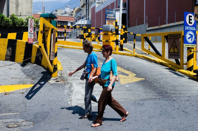 Señálame con color. The Art Of Street Photography Full Length Two People Men Males  Building Exterior Day Architecture Child City Real People Adult People Childhood Togetherness Street Casual Clothing Walking Road Mid Adult Built Structure EyeEm Best Shots EyeEm Selects Streetphotography Street Photography The Street Photographer - 2019 EyeEm Awards