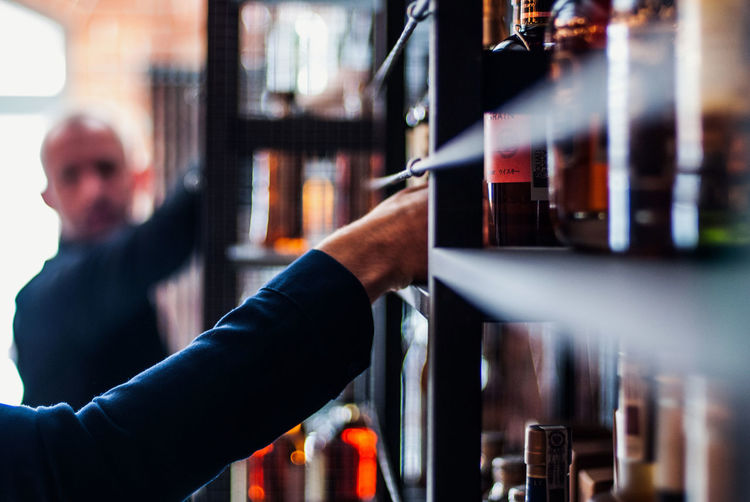 Cropped hand of man holding picking wine bottle from shelf