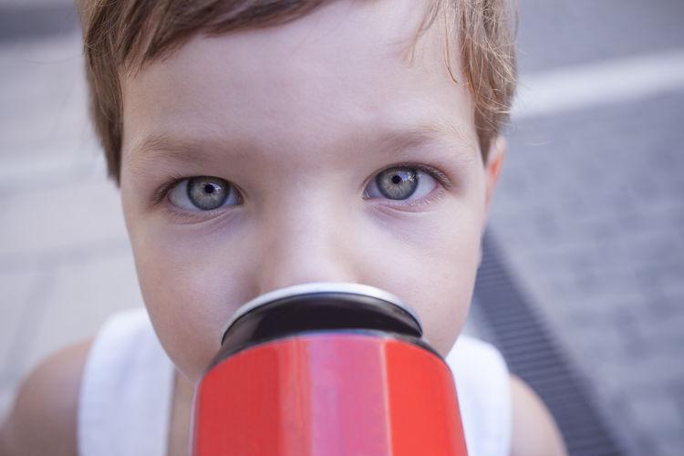 Close-up portrait of boy drinking coffee