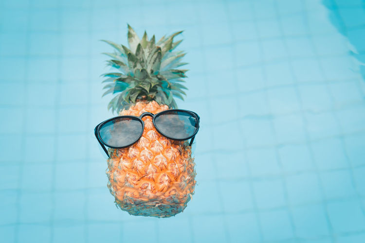 Pineapple wearing sunglasses in swimming pool., Summer and vacation concept. Glasses Blue Tile Indoors  Close-up Flooring No People High Angle View Day Directly Above Still Life Fashion Focus On Foreground Pattern Nature Tiled Floor Table Turquoise Colored Single Object Swimming Pool Personal Accessory Eyewear Pineapple Fruit Summer