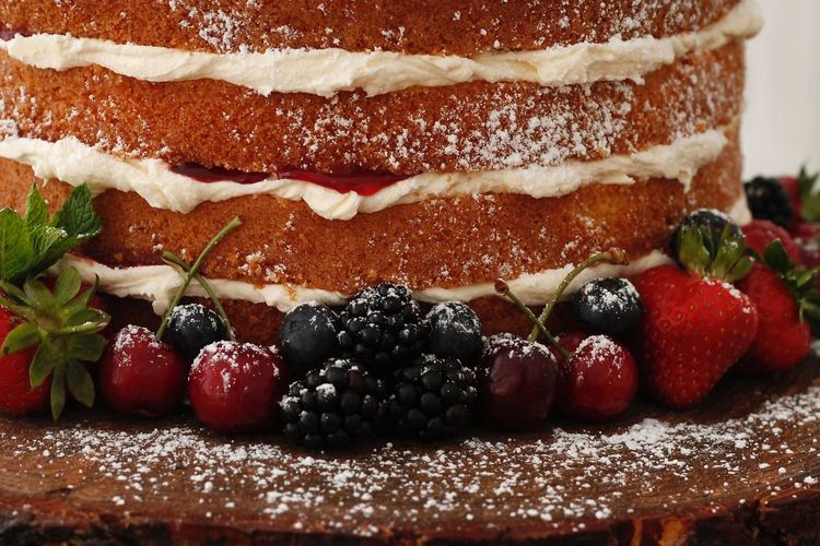 Close-Up Of Berry Fruits On Layered Sponge Cake