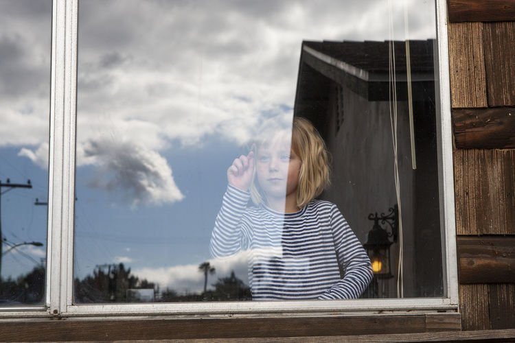 Woman standing by window against sky