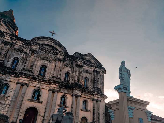 Low angle view of statue of historic building against sky