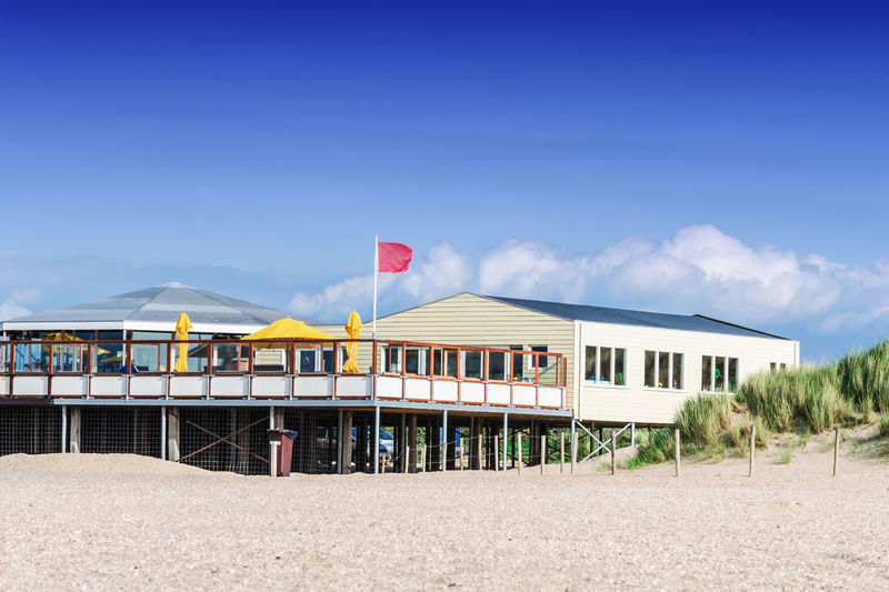 Beach restaurant pavilion in South Holland, Netherlands Pub Terrace Architecture Beach Beach Bars Beach Club Beauty In Nature Built Structure Cloud - Sky Coast Counter Day Flag Nature No People Outdoors Parasol Restaurant Sand Sky Tresen Street Cafe