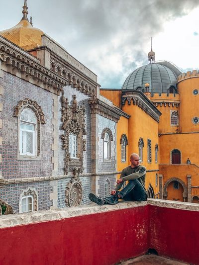 Man sitting outside historic building against sky