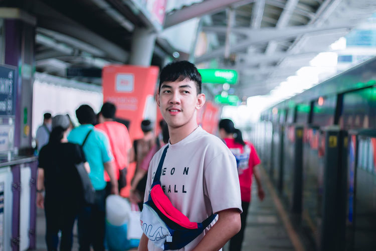 Lifestyles Real People Focus On Foreground Casual Clothing Waist Up Standing Leisure Activity Architecture Indoors  Men Incidental People Transportation Text Railroad Station Public Transportation Looking Teenager Waiting
