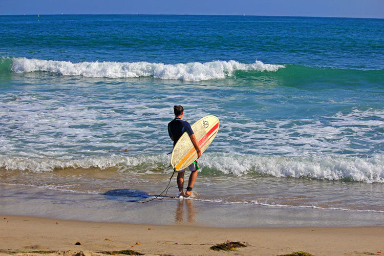 Rear view of woman holding surfboard on shore at beach