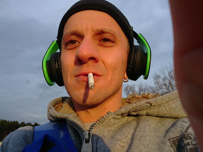 Low Angle Portrait Of Mid Adult Man Smoking Cigarette Against Sky