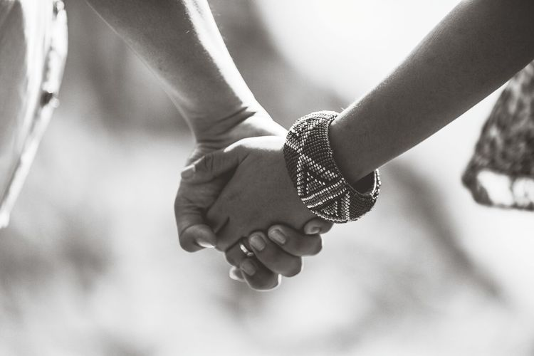 Close-up of hand holding hands against blurred background