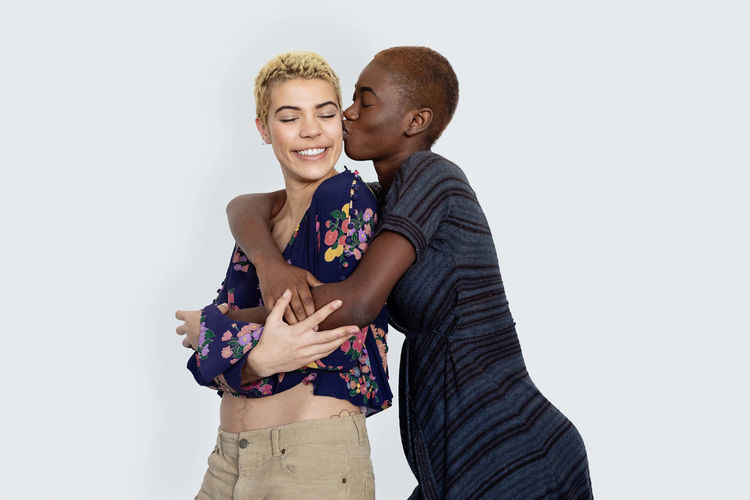 Woman kissing girlfriend against white background
