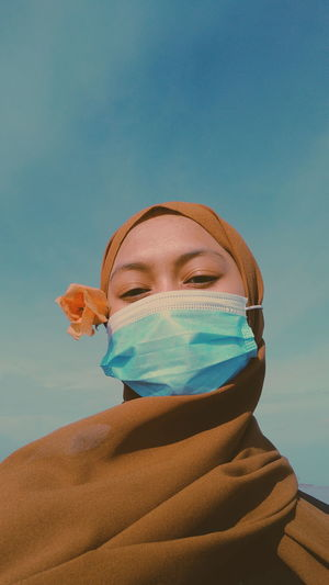 Low angle portrait of woman wearing mask and hijab against sky