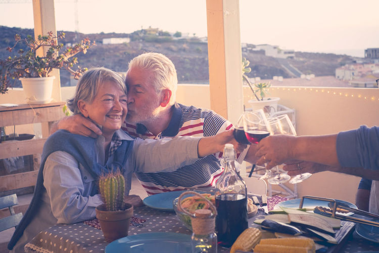 group of friends having dinner on the rooftop, couple kissing Vacations Adult Bonding Day Drink Drinking Drinking Glass Enjoyment Food And Drink Friendship Grey Hair Happiness Kissing Laughing Love Men Outdoors People Retirement Senior Couple Smiling Table Terraced Field Togetherness Two People
