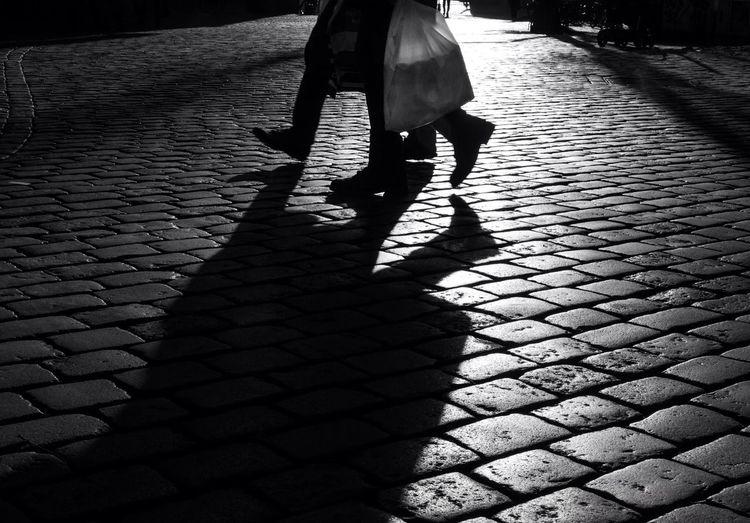 Shadow of woman on footpath