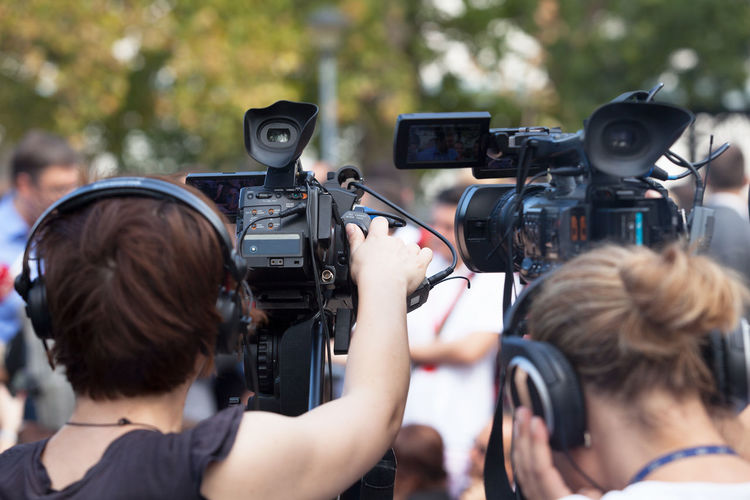 Rear view of women operating cameras during event
