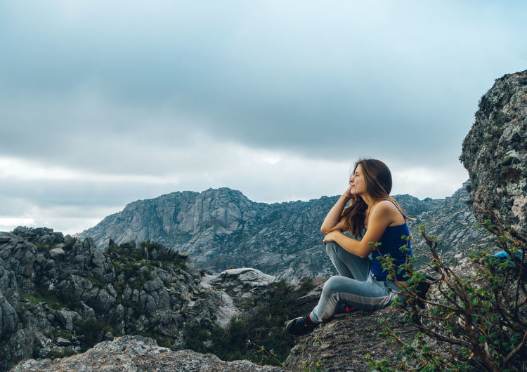 Smiling woman sitting on rock against mountain