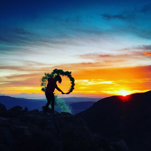 Side view of silhouette woman holding smoke bomb on mountain at sunset
