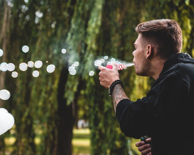 Man blowing bubbles while standing against trees