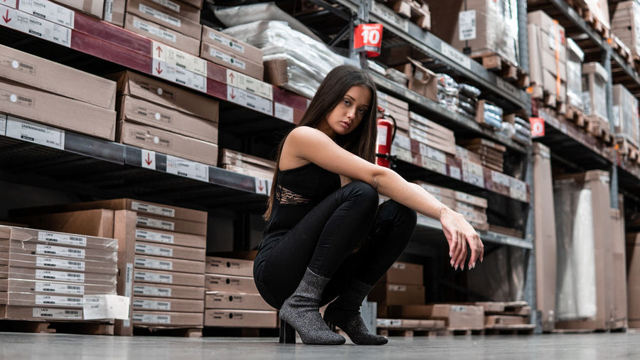 Full length portrait of young woman crouching on floor in warehouse