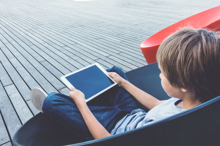 Boy using digital tablet while sitting on chair in school