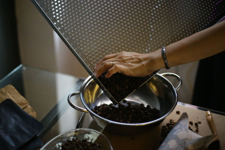 Close-up of human hand pouring chocolates in sieve