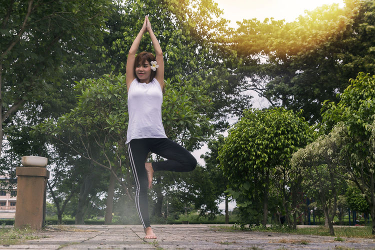 Full Length Of Young Woman Practicing Yoga At Public Park