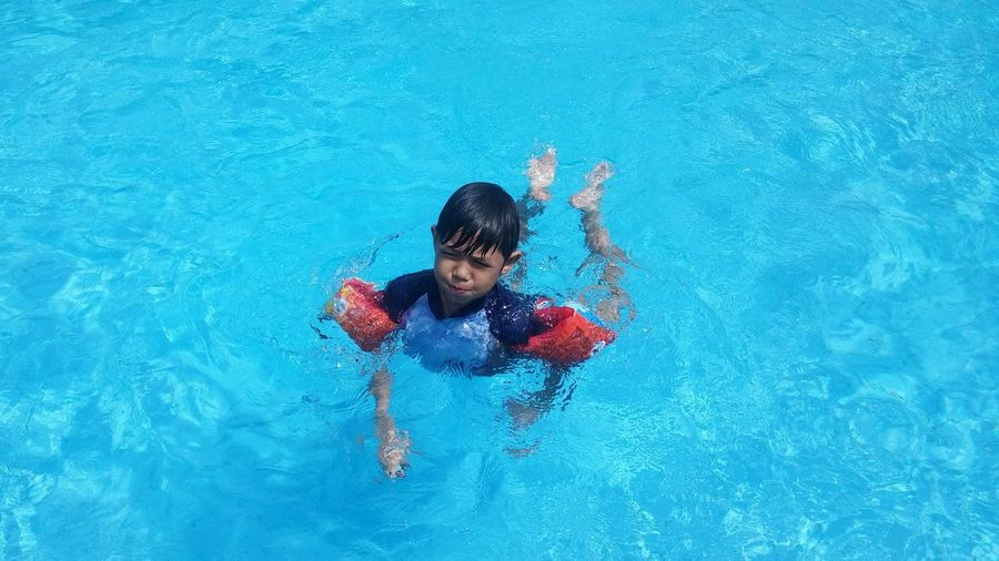 High Angle View Of Boy Wearing Water Wings Swimming In Pool