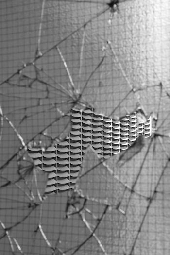 Close-up of broken window against wall
