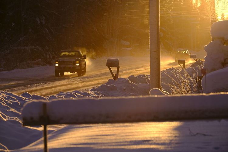 Car on snow covered road during sunset